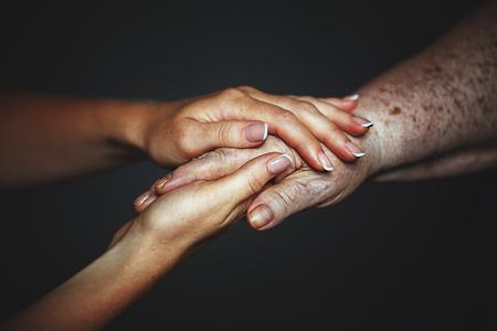 Het concept van de zorg voor ouderen en gepensioneerden. Handen van de oude en een jonge vrouw