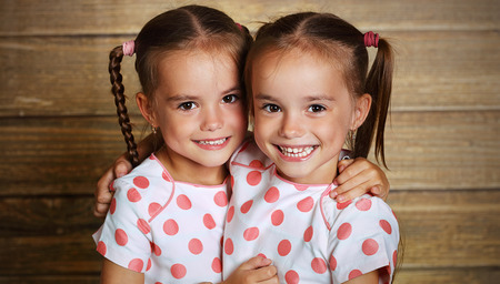 happy family children twin sisters hugging and laughing 스톡 콘텐츠