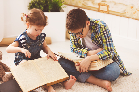 ber: children brother and sister, boy and girl reading a book at home Stock Photo