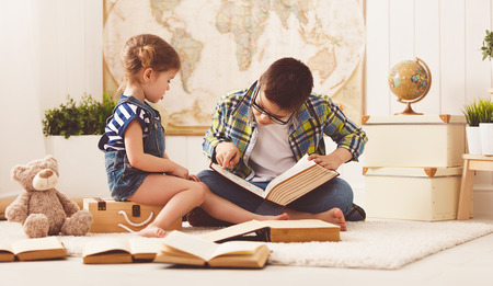 children brother and sister, boy and girl reading a book at home Stock Photo