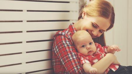 mama e hijo: madre de familia feliz y bebé que juegan en la ventana de su casa
