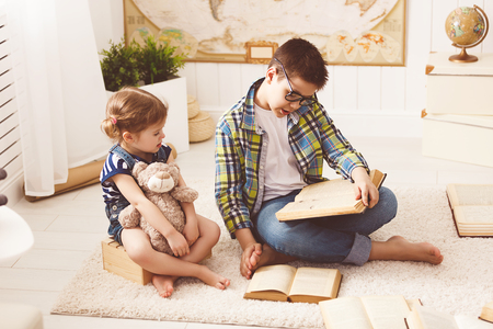 toy story: children brother and sister, boy and girl reading a book at home Stock Photo