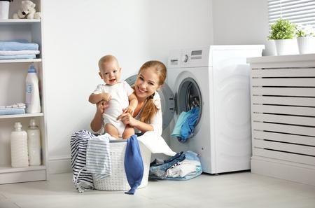 어머니 세탁에 종사하는 아기와 주부는 세탁기에 옷을 접어 스톡 콘텐츠