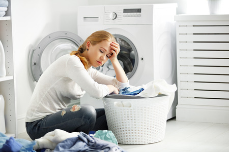 tired unhappy woman housewife is engaged in the laundry, fold clothes into the washing machine