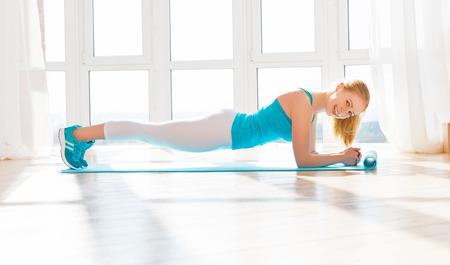 gelukkig gezond vrouw beoefenen en geëngageerde sport en fitness naar huis