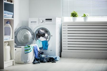 wasserette. Een wasmachine en een stapel vuile kleding thuis Stockfoto