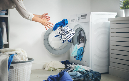 overburden: laundry concept. dirty clothes flies into the washing machine