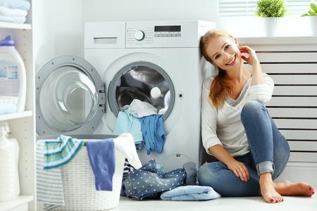 gelukkige vrouw huisvrouw in de wasruimte in de buurt van de wasmachine met vuile kleren