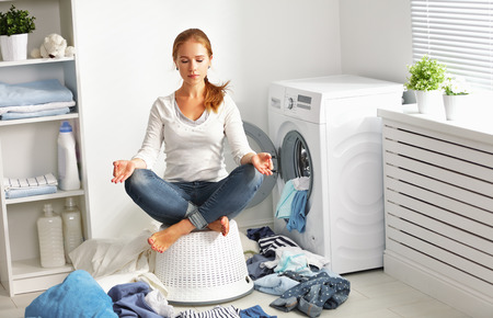 dirty room: concept. tired housewife meditates in lotus position in laundry room near washing machine and dirty clothes
