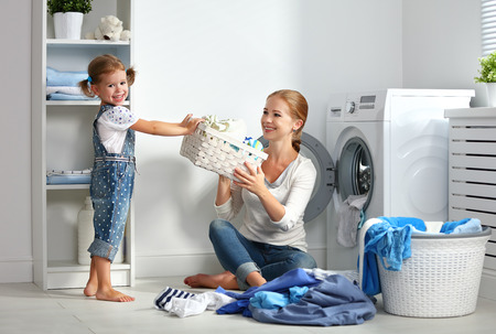 machines: family mother and child girl little helper in laundry room near washing machine and dirty clothes