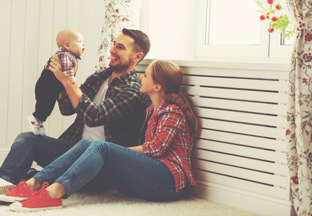 happy family mother and father playing with a baby at home Stock Photo