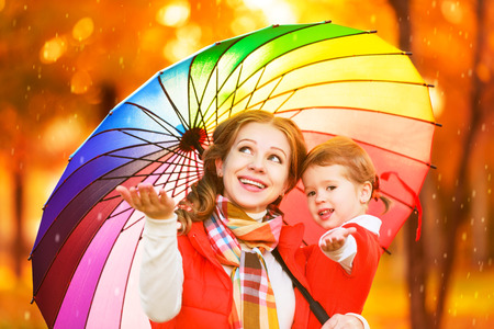 happy woman with rainbow multicolored umbrella under rain on nature in the park Stock Photo