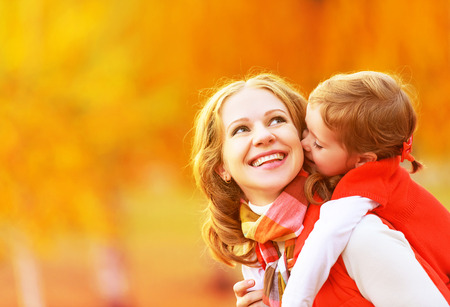 happy family nature: happy family. mother and child little daughter play kissing on autumn walk in nature outdoors