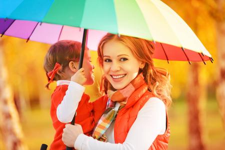 sotto la pioggia: Felice famiglia mamma e figlia bambino con arcobaleno colorato ombrello sotto la pioggia sulla natura