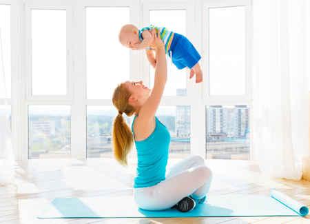 sports mother is engaged in fitness and yoga with a baby at home Stok Fotoğraf - 62009999