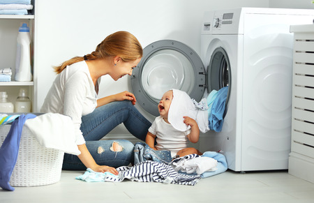 appliance: mother a housewife with a baby engaged in laundry fold clothes into the washing machine