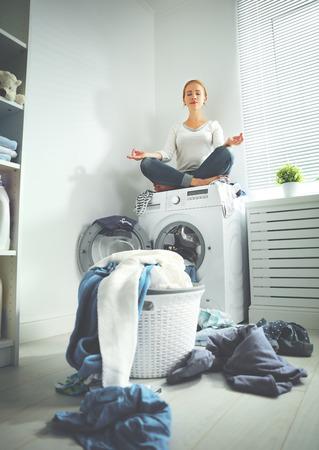 concept. vermoeide huisvrouw mediteert in lotushouding in de wasruimte in de buurt van een wasmachine en een vuile kleren