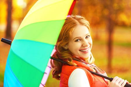 happy woman with rainbow multicolored umbrella under rain on nature in the park Stock Photo