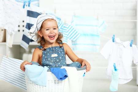 child fun happy little girl  to wash clothes and laughs in the laundry room Stok Fotoğraf - 62010479