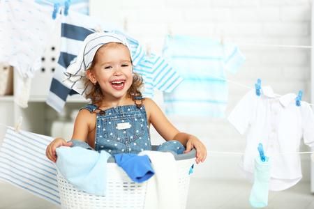 limpieza: niño de la diversión niña feliz para lavar la ropa y se ríe en la lavandería