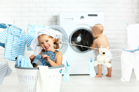 helpers: little helpers funny kids happy sister and brother in the laundry to wash clothes, playing and laughing