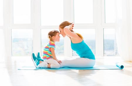 가족 어머니와 자식 딸은 집에서 피트니스, 요가, 운동에 참여하고있다 스톡 콘텐츠