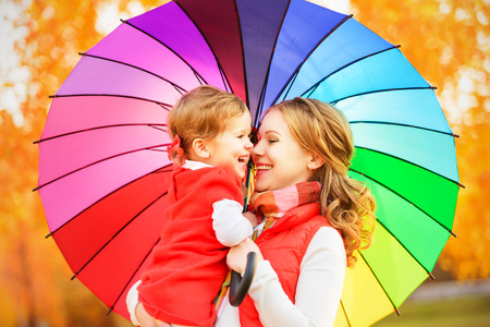happy family nature: Happy family mum and child daughter with rainbow colored umbrella under rain on nature