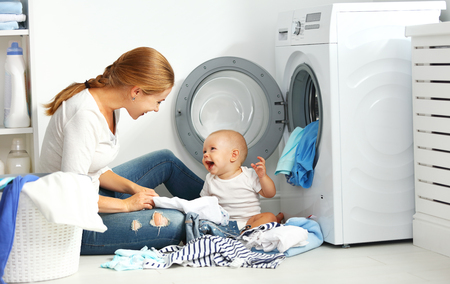 chores: mother a housewife with a baby engaged in laundry fold clothes into the washing machine