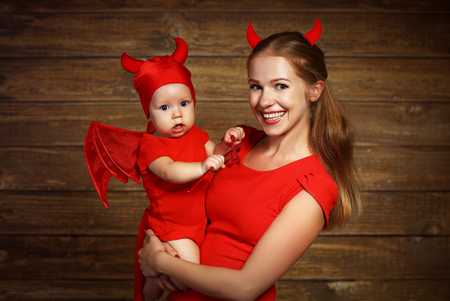 devil woman: Family fun mother and baby son having fun and celebrate Halloween in devil costume