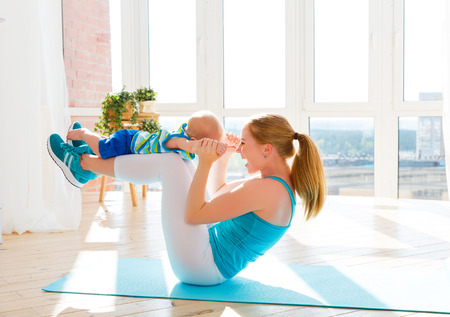 sports mother is engaged in fitness and yoga with a baby at home Imagens - 62638558
