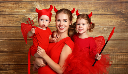 happy family with masquerade costumes devil prepares for Halloween