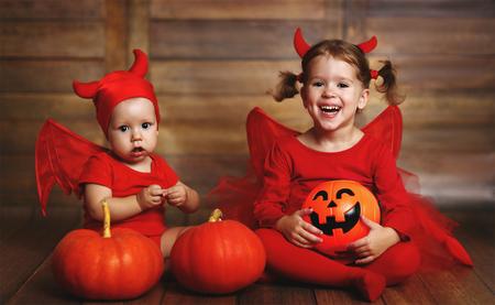 pitchfork: fun happy children are devil costume with pumpkins prepared for Halloween Stock Photo