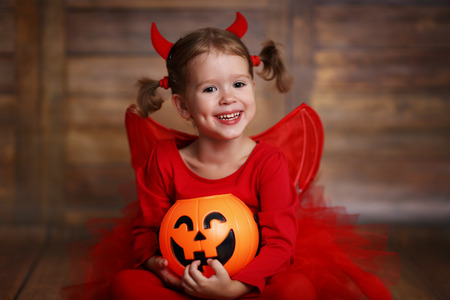 funny child girl in devil halloween costume with pumpkin on a dark wooden background