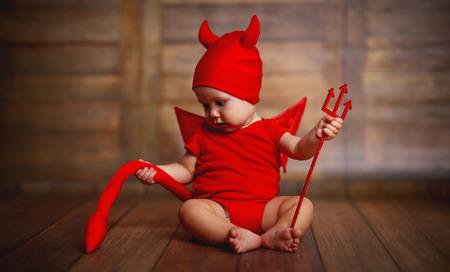 satan: lustiges Baby in den Teufel Halloween-Kostüm mit Hörnern und Dreizack auf einem dunklen Holz Hintergrund