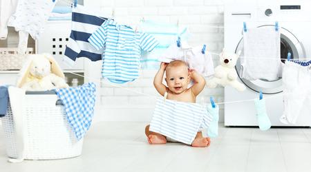 fun heureux petit garçon pour laver les vêtements et les rires dans la salle de lavage