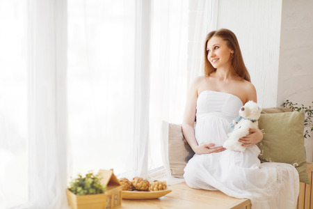 wait: gentle elegant pregnant woman in a white dress flying