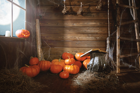 Halloween background. old wooden hut witches barn with pumpkins, cobwebs, magic book, broom
