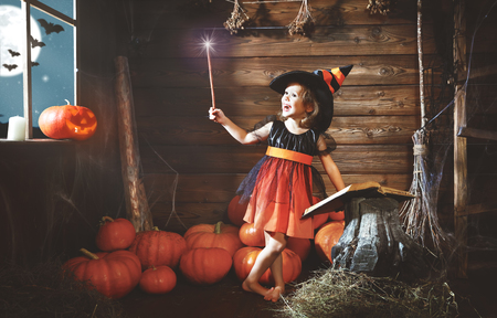 spells: child little witch with magic wand and reading a magical book of spells in the old hut Stock Photo