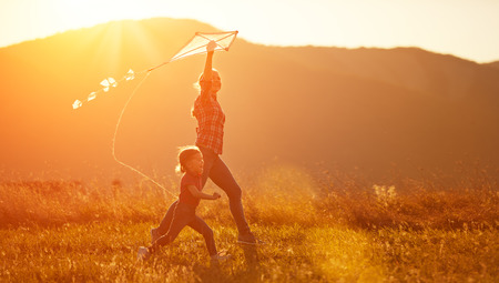 gelukkig gezin moeder en kind lopen op de weide met een vlieger in de zomer op de aard