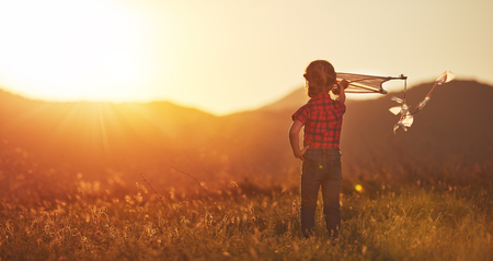 happy child girl with a kite on meadow in summer in nature