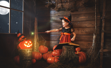 spells: child little witch with magic wand, pumpkin Jack and magical book of spells in the old hut Stock Photo