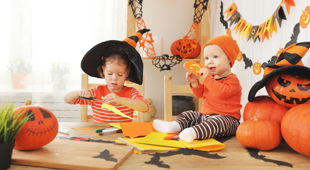 happy kids preparing for Halloween decorated home bats handmade of paper Stock Photo