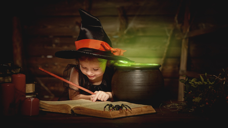 pocion: Halloween. child girl witch preparing a potion in the cauldron