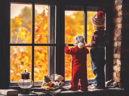 Niños felices hermano y hermana mirando por las ventanas en el otoño