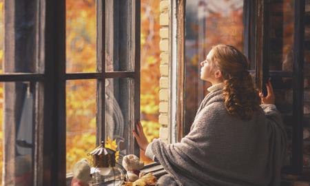 Feliz mujer joven disfrutando del aire fresco de otoño en la ventana abierta Foto de archivo - 63077166