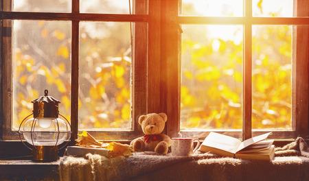 秋。秋と居心地の良い窓辺の葉、本、お茶のマグ