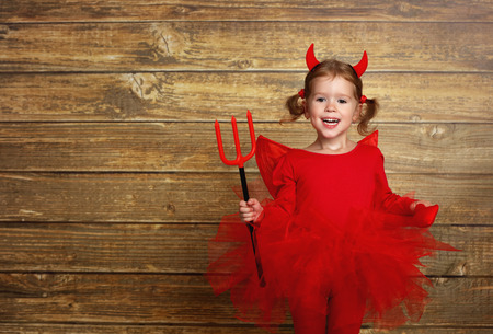 trident: funny child girl in devil halloween costume with horns and trident on a dark wooden background