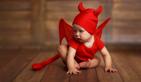 unruly: funny baby in devil halloween costume with horns on a dark wooden background Stock Photo