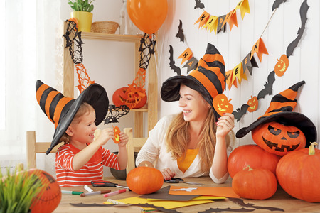 family mother and child daughter are preparing for Halloween cut a pumpkin and bat of colored paper and decorate the home