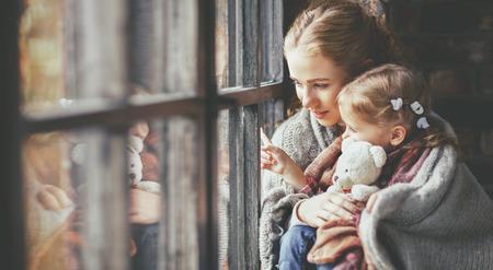 familie moeder en kind dochter warm houden en kijk uit het raam op een regenachtige herfstdag